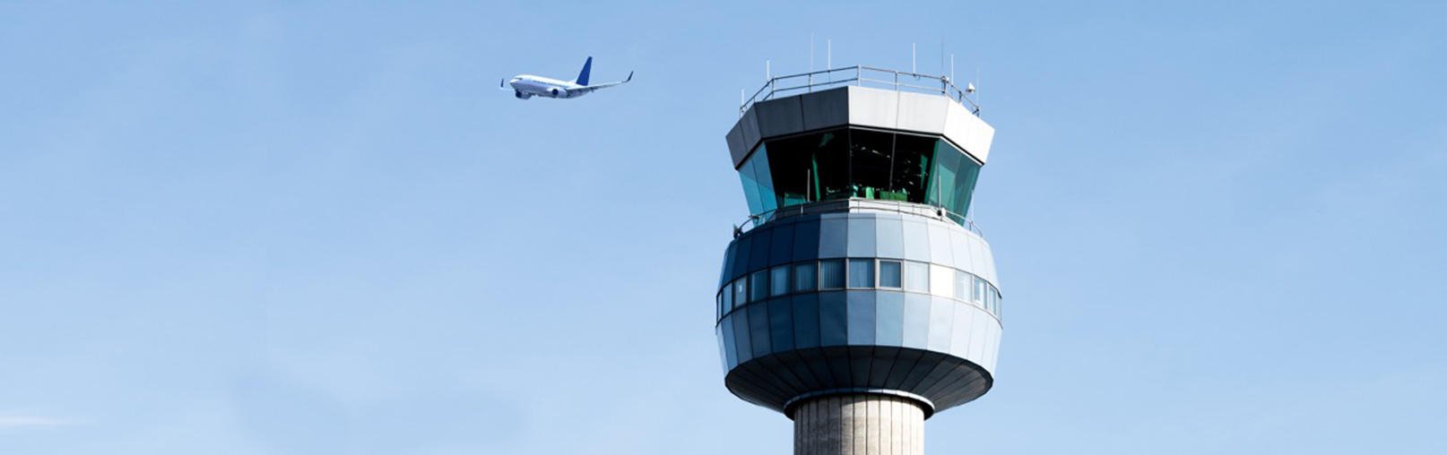 silouette of departing aircraft by control tower